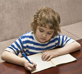 Child writing in notebook — Stock Photo