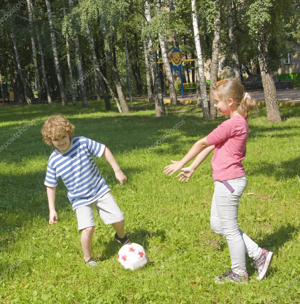 Children boy and girl playing football on yard on grass, birch trees around. — Stock Photo #14125518