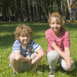 Children sitting on grass — Stock Photo #15874559