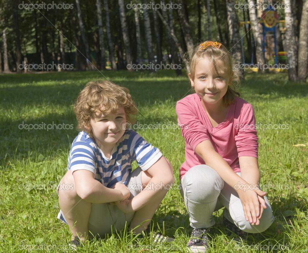 Boy and girl school age Caucasian sitting on grass together near birch trees. — Stock Photo #15874559