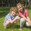 Boy and girl sitting on grass — Stock Photo