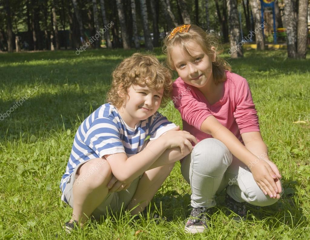 Boy and girl school age Caucasian sitting outdoors on grass near birch trees. — Stock Photo #16041425