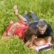 Couple with notebook on grass — Stock Photo