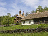 Village house and wooden church — Stock Photo