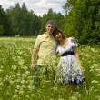 Young couple (man and woman) on a meadow in blossom — Stock Photo
