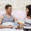 Woman brings man breakfast in bed — Stock Photo