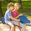 Boy and girl on swing — Stockfoto