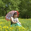 Lady with parasol and yellow dandelions — Stock Photo #30622033