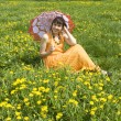 Woman with parasol and yellow dandelions — Stock Photo #30623113