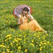Stock Photo: Woman with parasol and yellow dandelions