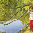 Stock Photo: Womwith willow tree and lake