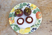 Mangosteen on plate over granite surface — Stock Photo