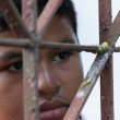 Stock Photo: Boy Behind Iron Lattice