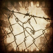 Concept old grunge film strip frame and wire fence background — Stock Photo