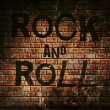 Rock and roll music word on red wall background — Stock Photo #42141157