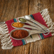 Selection of colorful spices in measuring spoons on an old worn — Stock Photo #41698461