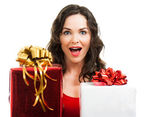 Surprised woman holding Christmas presents — Stock Photo