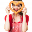 Happy woman looking through bread love heart — Stock Photo