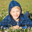 Smiling young boy lying in grass smiling — Stock Photo