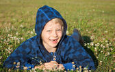 Happy boy lying in grass smiling — Stock Photo