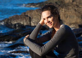 Happy woman sitting on the coast — Stockfoto