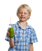 Boy pulling face holding green smoothie — Stock Photo