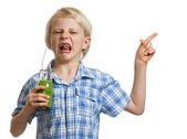 Disgusted boy with green smoothie pointing — Stock Photo