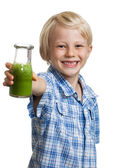 Happy boy holding bottle of green smoothie — Stock Photo