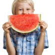 Cute boy peeking behind water melon — Stock Photo #33591687