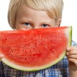Happy smiling boy holding slice of watermelon. — Stock Photo #33592221