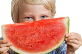 Close-up of boy peeking over water melon — Stock Photo