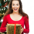 Surprised women holding Christmas present — Stockfoto