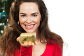 Beautiful woman holding out Christmas gift — Foto Stock