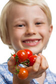 Cute boy holding out bunch of tomatoes — Stock Photo