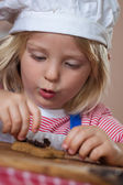 Cute young boy putting raisins on gingerbread — Stock Photo