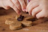 Child putting raisins on gingerbread man — Stock Photo