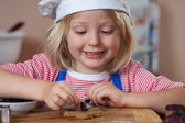 Cute smiling boy putting raisins on gingerbread — Stock Photo