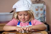 Cute boy making gingerbread man — Stock Photo