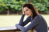 Sad depressed woman sitting outdoors — Stock Photo