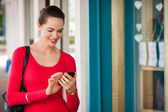 Smiling woman texting on mobile phone — Stock Photo
