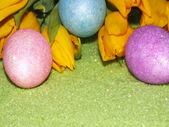 Colorful easter eggs with yellow flower in green stones — Stock Photo