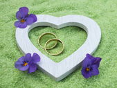 White heart and wedding rings made of wood with delicate blossoms in small stones — Stock Photo