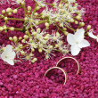 Foto Stock: Wedding rings made of wood with delicate blossoms in small stones