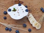 Yogurt with fruit on a board of oak in the garden — Stock Photo