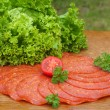 Sliced sausage on a board from oak — Stock Photo
