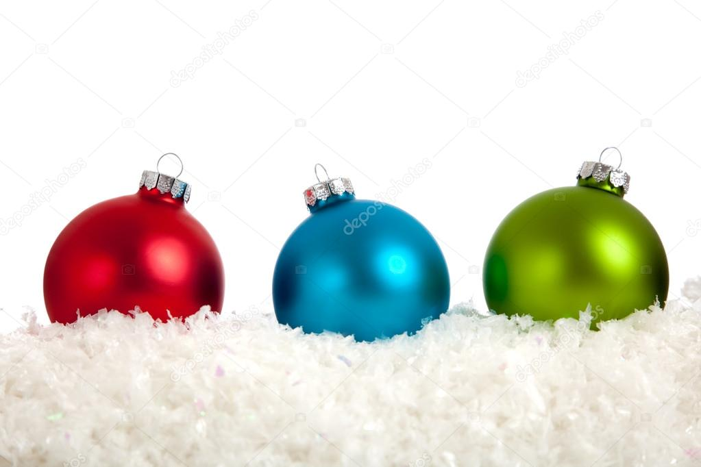 A group of colorful Christmas Baubles on a white background with copy space and fake snow — Stock Photo #13384571
