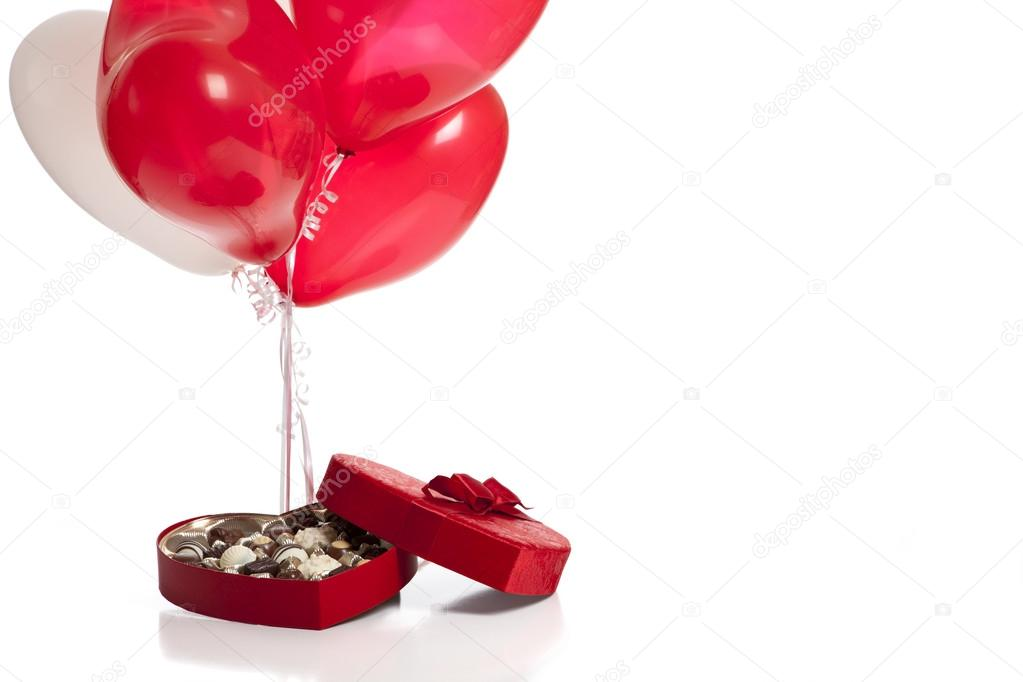 A Valentines day background consisting of chocolates in a heart shaped box and heart shaped balloons on a white background — Stock Photo #13397314