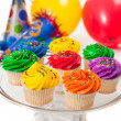 Cupcakes, balloons and party hats on a white background — Stock Photo