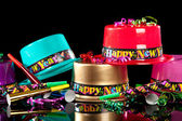 New Years' Eve party hats on black background — Stock Photo