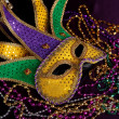 Stock Photo: Mardi gras mask and beads on purple background